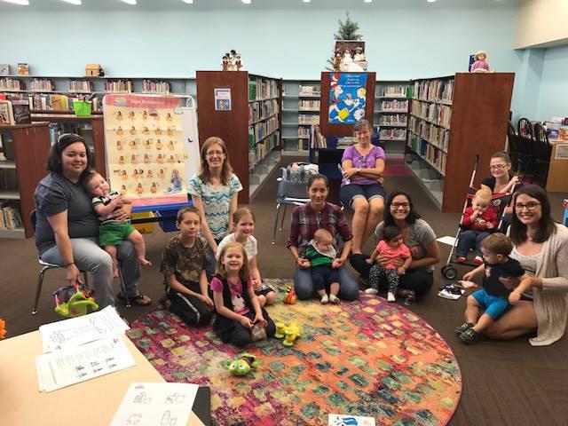 Niños y adultos alrededor de una alfombra colorida después de Cuentos y señas para bebés