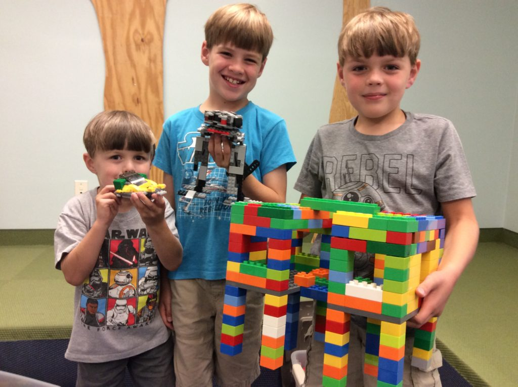 Three young patrons with their LEGO brick creations.