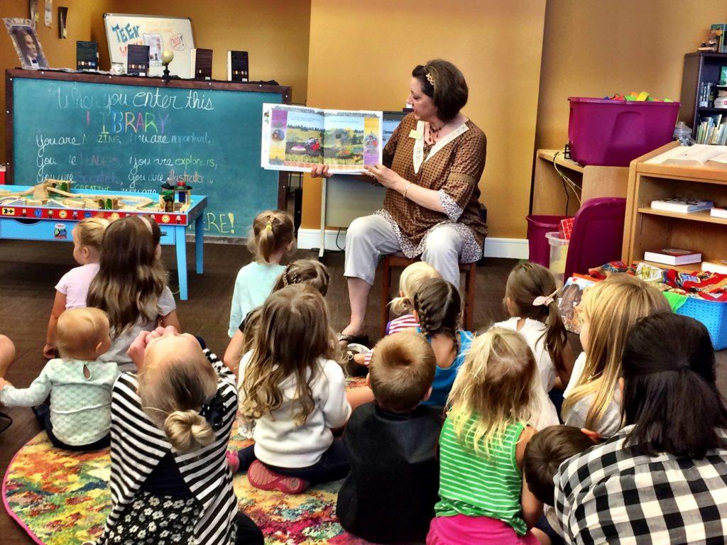 Niños escuchando atentamente a la bibliotecaria de niños leerles una historia.
