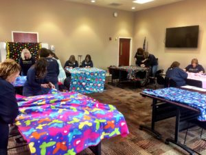Community members working together to create fleece blankets to provide to Calhoun's foster kids.