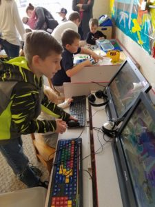 A child helping a younger child on the computers with other activities in the background.