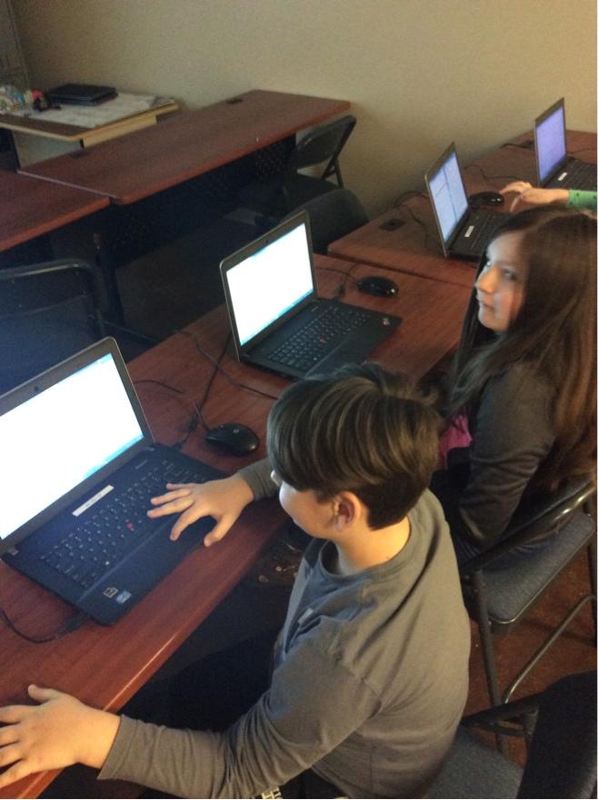 Preadolescentes frente a una computadora durante el club de códigos.