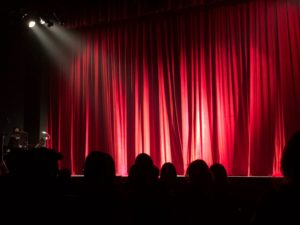 Stage with red curtains and a spotlight.