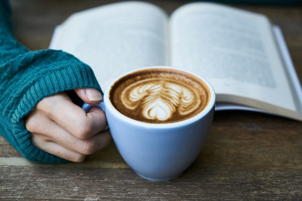 Hand holding a coffee mug in front of a book.