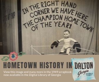 "A doll in a boxing ring with the words ""In the right hand corner we have here the champion hometown of the year!"