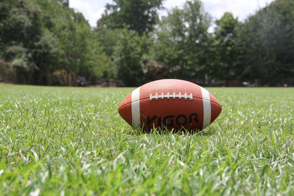 Bola de fútbol americano sobre un campo.