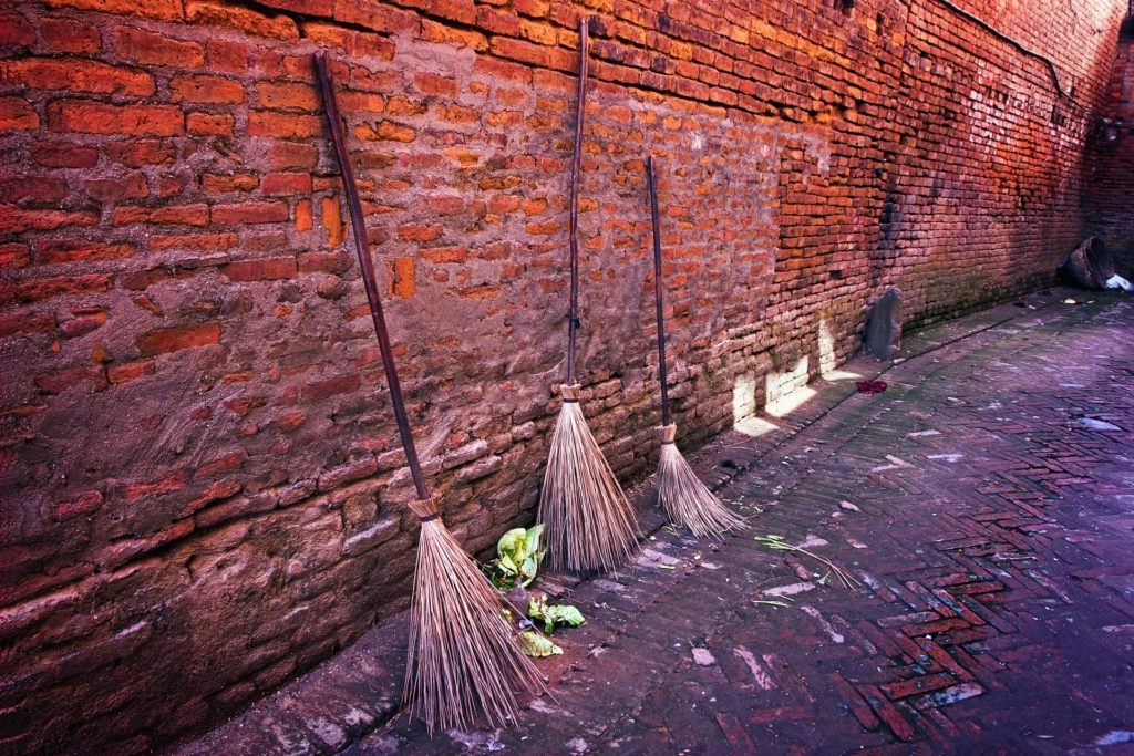 Brooms against a brick wall.