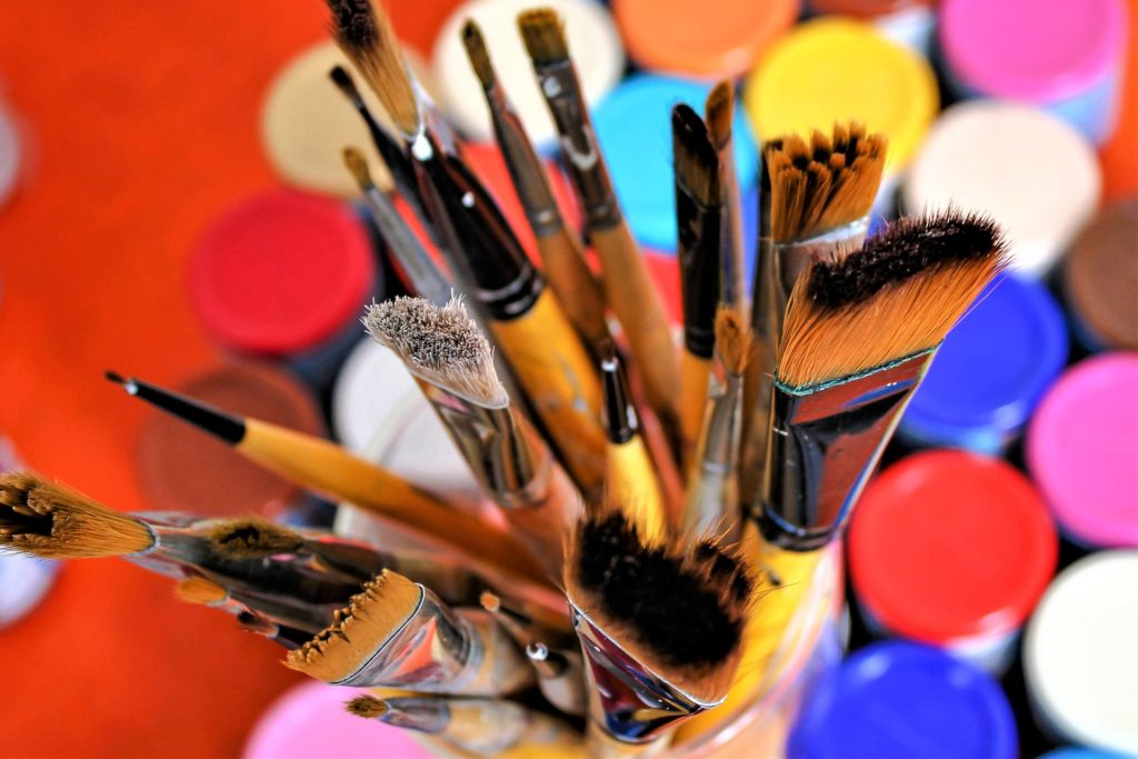 Paintbrushes with colorful paint lids.