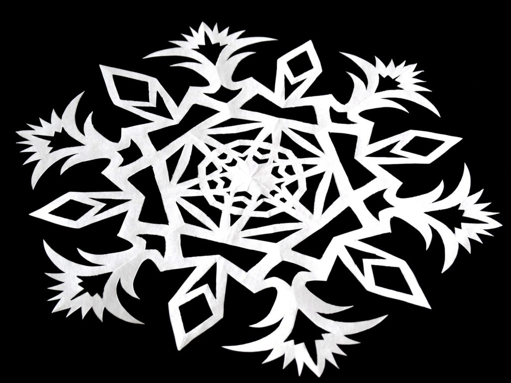 A paper snowflake on a black background.