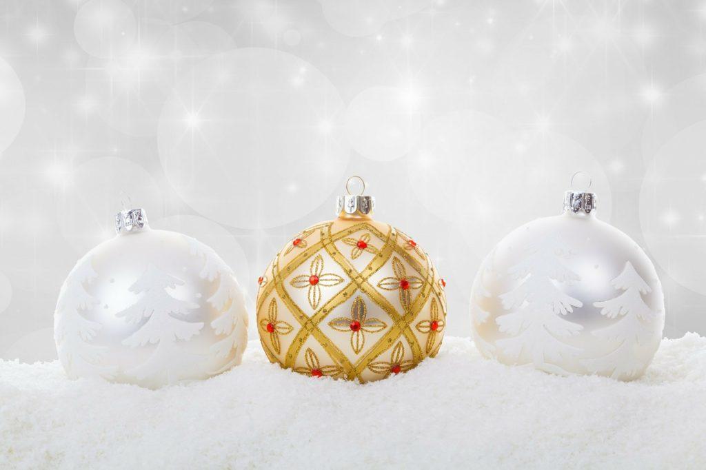 Dos adornos navideños con árboles blancos y uno dorado.
