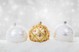 Two christmas ornaments with white trees and one gold one.