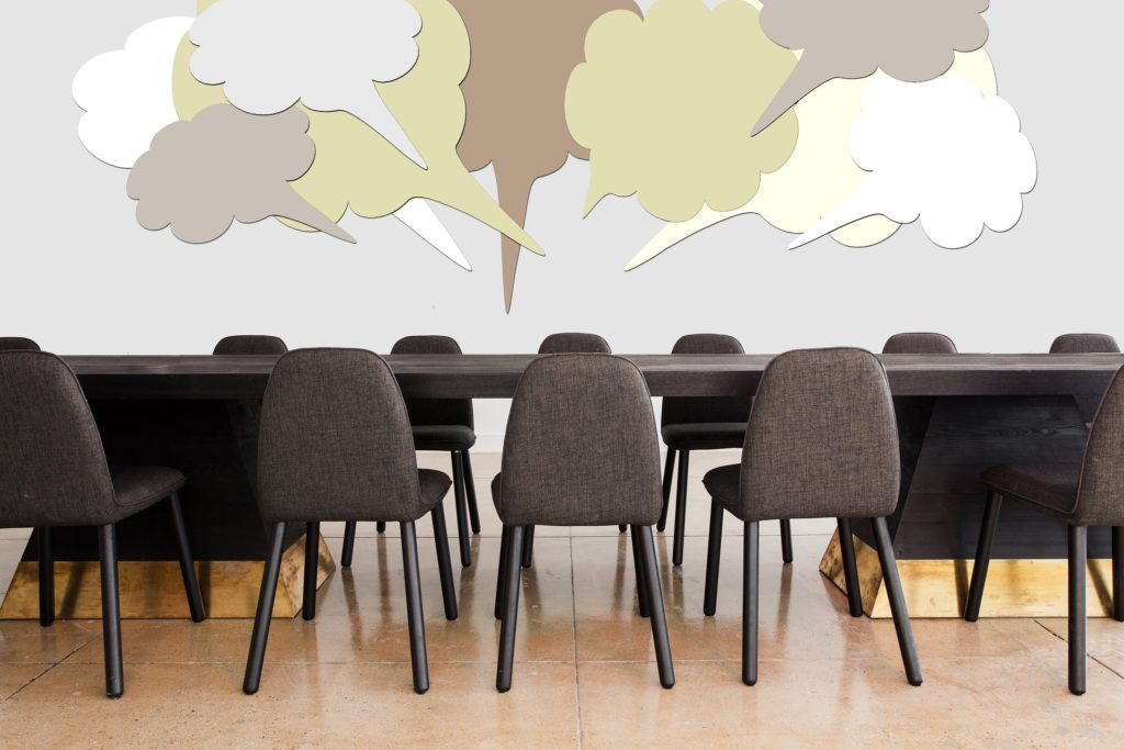 Conference table and chairs with speech bubbles.