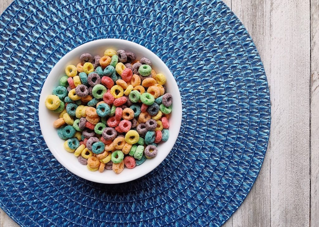 Bowl of fruit loops or similar cereal on a blue placemat