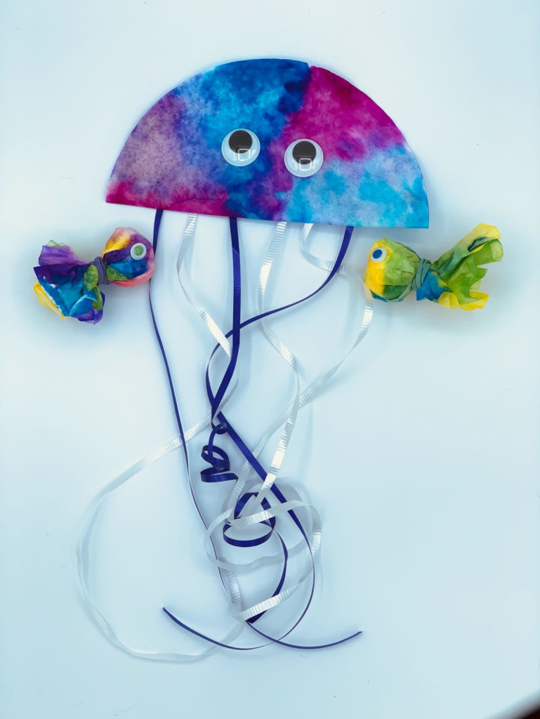 A purple and blue jellyfish made from coffee filters and ribbon accompanied by two small coffee filter fish.