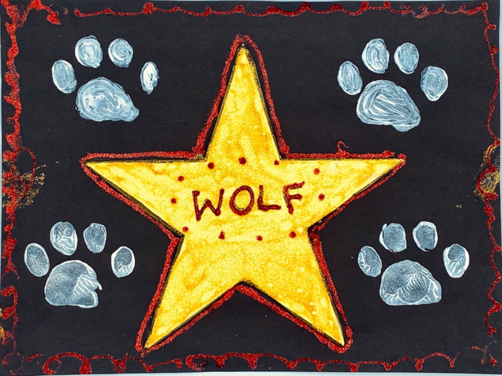 Painted golden star that says Wolf on a black background with white paw prints.