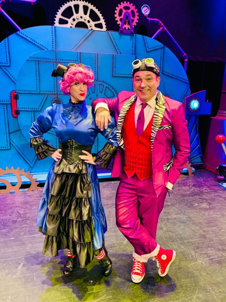 Man and woman standing together in blue and pink steampunk clothing.