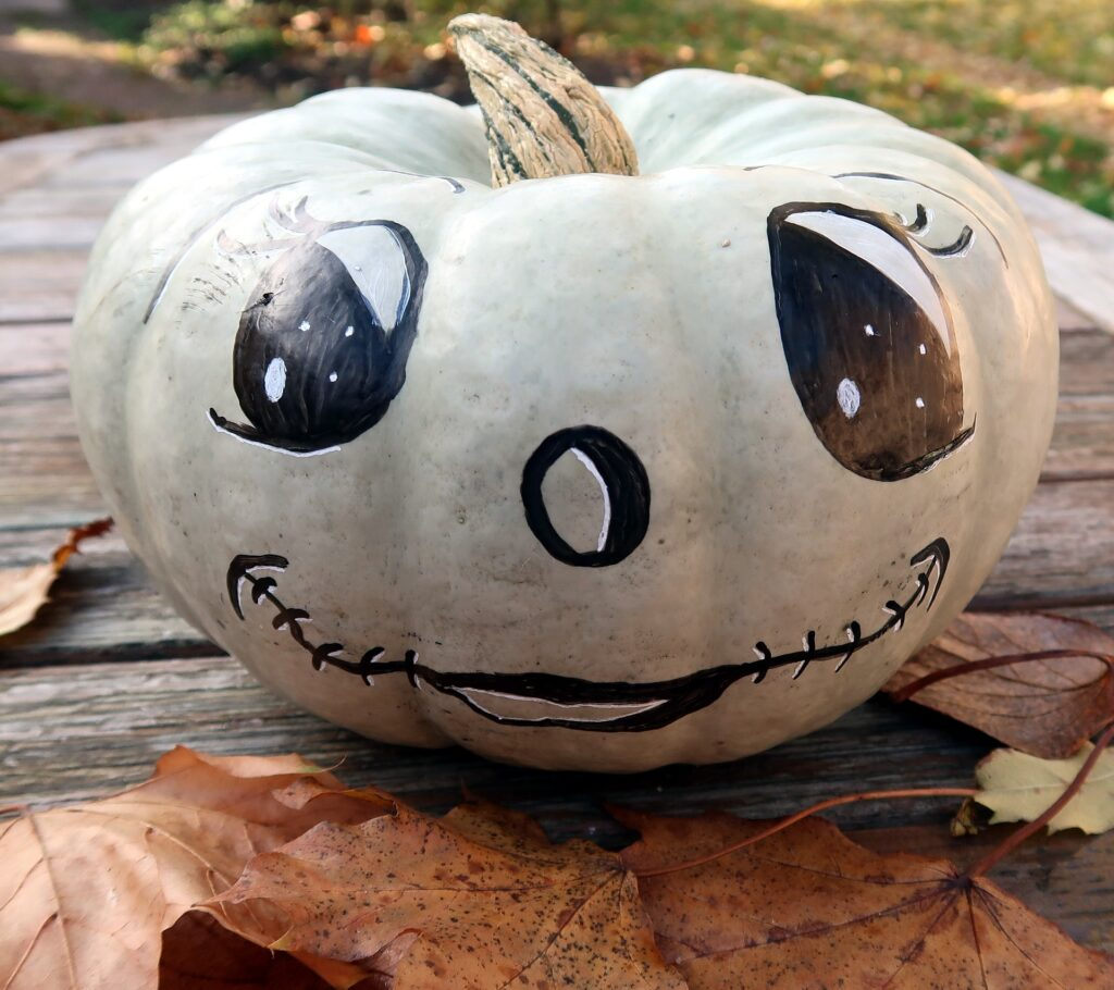 White pumpkin with painted eyes, nose, and mouth.